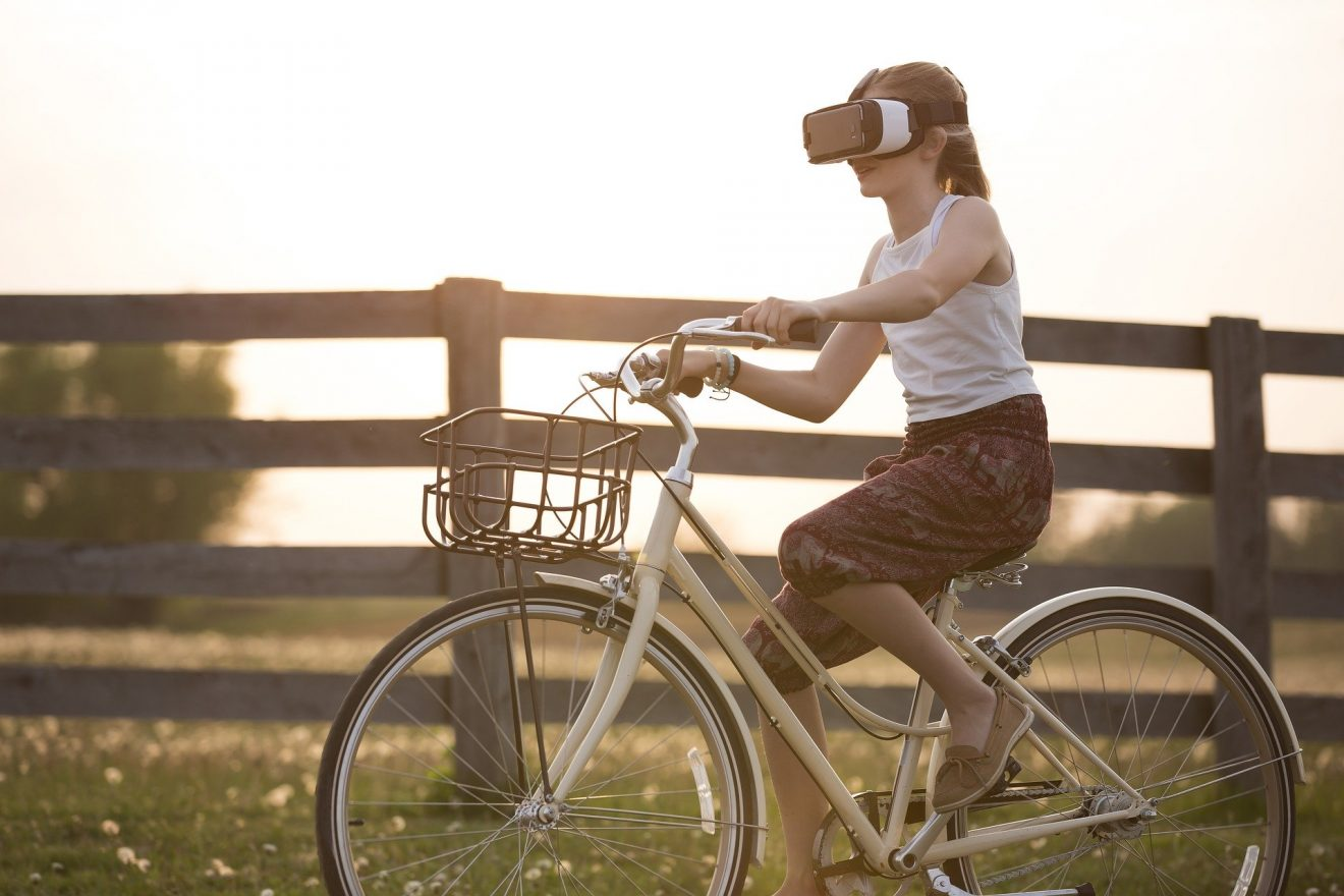 Girl wearing a virtual reality headset while riding bike.