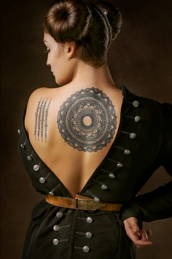 A vintage portrait of a woman with a Mandala tattoo