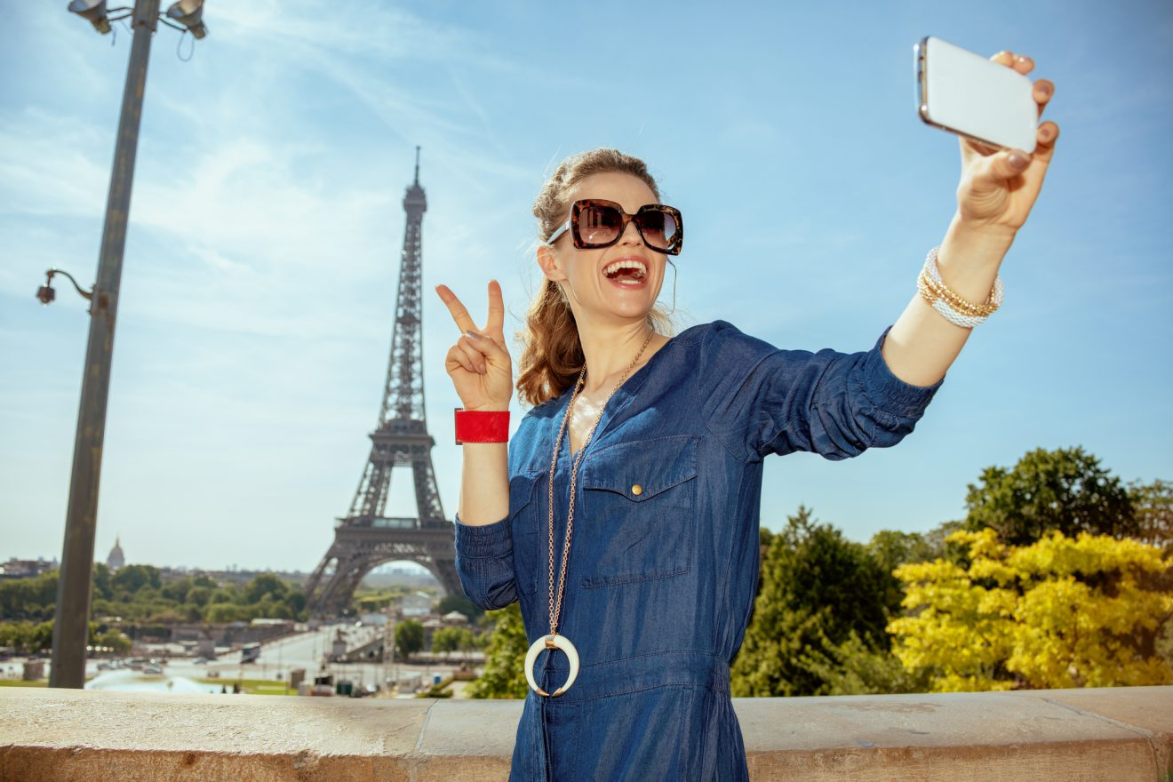 happy young woman in blue jeans overall taking selfie with smartphone and showing victory gesture against clear view of the Eiffel Tower in Paris, France.