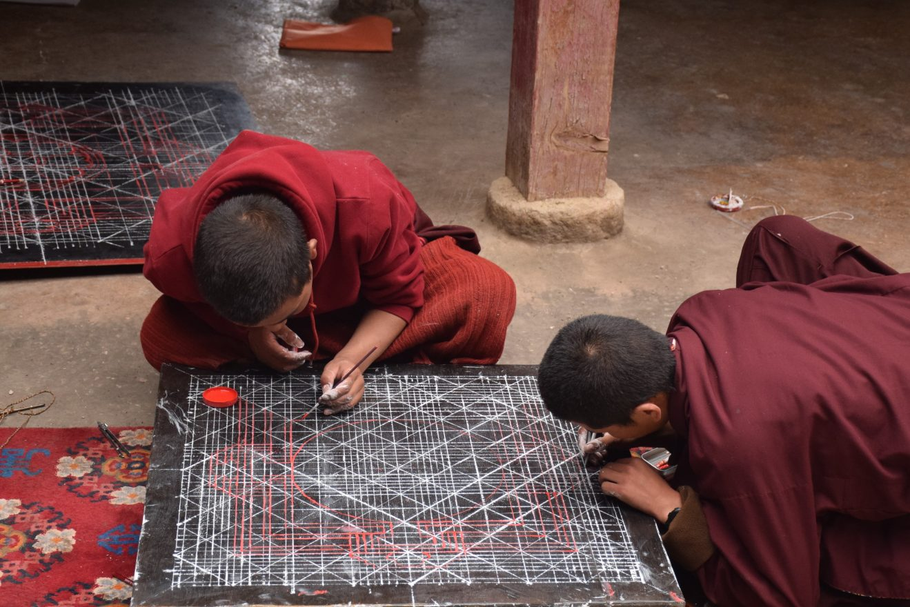 Buddhist monks practicing drawing a mandala inside Sakya monastery, Tingri county, Tibet - China