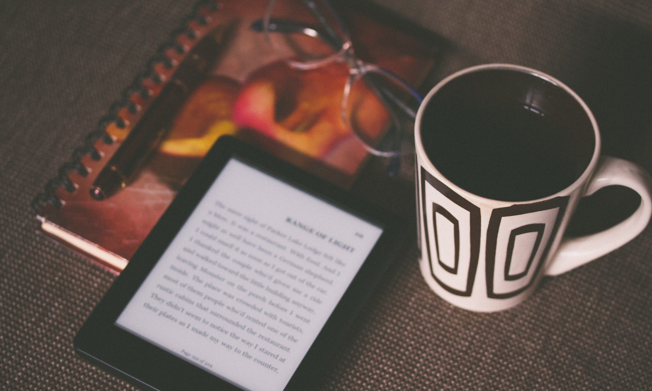 E-book reader next to coffee and notebook. Image courtesy: https://www.pxfuel.com/en/free-photo-oefjd